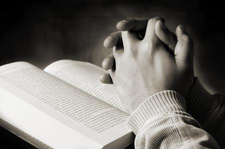 Handen van een persoon die zegt gebed van een heilig boek