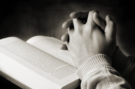 confession: Hands of a person saying prayer from a holy book