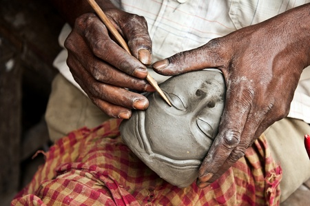 An artisan creates the head of a goddess for Durga puja festival in Bengal, India
