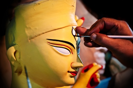sculptor: An artist drawing the face of goddess Durga made of clay