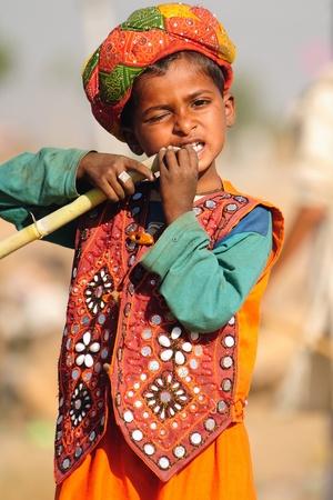 PUSHKAR, INDIA - NOVEMBER 7: A Rajasthani boy dressed in ethnic clothes enjoys sugarcane at the Pushkar cattle fair on November 7, 2011 in Pushkar, Rajasthan, India.