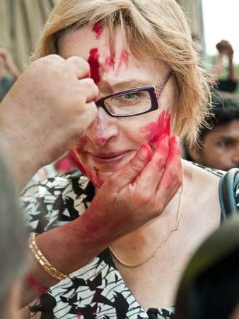 CALCUTTA - OCTOBER 6: A foreign tourist gets a warm cultural greeting with vermilion at Sindur Khela traditional ceremony on the final day of Durga Puja festival on October 6, 2011 in Calcutta, India Stock Photo - 11952114