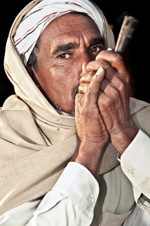 PUSHKAR, INDIA - NOVEMBER 7: A camel trader smokes at the Pushkar cattle fair on November 7, 2011 in Pushkar, Rajasthan, India. Pilgrims and camel traders flock to the holy town for the annual fair. Editorial