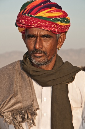 PUSHKAR, INDIA - NOVEMBER 8: A Rajasthani tribal man wearing traditional colorful turban attends the annual Pushkar Cattle Fair on November 8, 2011 in Pushkar, Rajasthan, India.