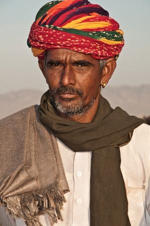 PUSHKAR, INDIA - NOVEMBER 8: A Rajasthani tribal man wearing traditional colorful turban attends the annual Pushkar Cattle Fair on November 8, 2011 in Pushkar, Rajasthan, India.