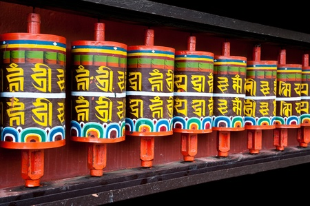 buddhism prayer belief: Row of colorful buddhism prayer wheels at a monastery in Sikkim Stock Photo