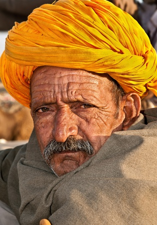 PUSHKAR, INDIA - NOVEMBER 8: A nomadic camel trader wearing traditional colorful turban attends the annual Pushkar Cattle Fair on November 8, 2011 in Pushkar, Rajasthan, India.