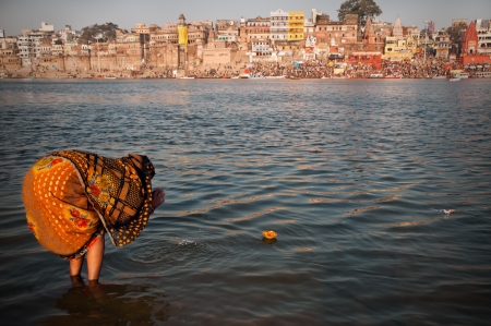 benares: VARANASI, INDIA - FEBRUARY 20, 2012: An Unidentified pilgrim offers prayer to holy Ganges river on Maha Shivaratri festival on February 20, 2012 at Varanasi, Uttar Pradesh, India.