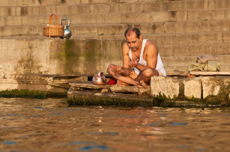 VARANASI, INDIA - FEBRUARY 19, 2012: A Hindu brahmin priest offers prayers on the bank of holy Ganges river on the auspicious Maha Shivaratri festival on February 19, 2011 at Varanasi, Uttar Pradesh, India Stock Photo - 13626986