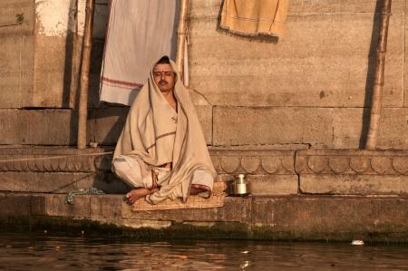 VARANASI, INDIA - FEBRUARY 19, 2012: A Hindu brahmin monk meditates on the bank of holy Ganges river on the auspicious Maha Shivaratri festival on February 19, 2011 at Varanasi, Uttar Pradesh, India