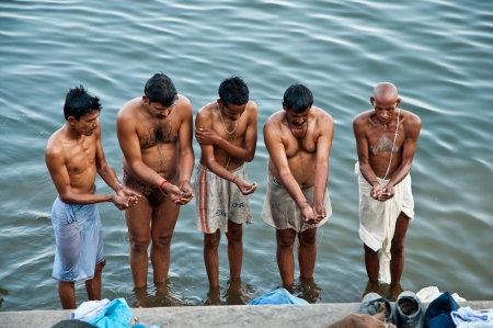 VARANASI, INDIA - FEBRUARY 18, 2012: Hindu pilgrims offer prayers on the bank of holy Ganges river on the auspicious Maha Shivaratri festival on February 18, 2011 at Varanasi, Uttar Pradesh, India.