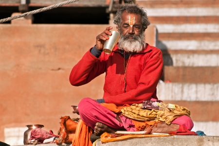 VARANASI, INDIA - FEBRUARY 19, 2012: A Hindu brahmin priest takes a break from prayer to drink water on the auspicious Maha Shivaratri festival on February 19, 2011 at Varanasi, Uttar Pradesh, India.