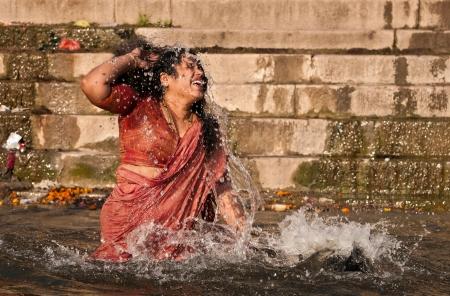 VARANASI, INDIA - FEBRUARY 19, 2012: Hindu pilgrim takes holy dip in river Ganges on the auspicious Maha Shivaratri festival on February 19, 2011 at Varanasi, Uttar Pradesh, India.
