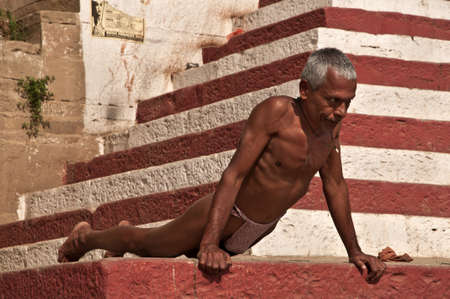An indian wrestler performs push-ups excercises at Ganges river bank on February 20, 2011  in Varanasi, Uttar Pradesh, India