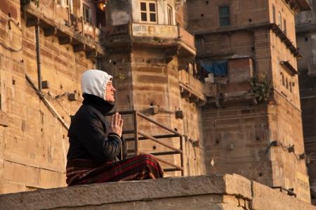 VARANASI, INDIA - FEBRUARY 20, 2012: An unidentified monk prays to the sun god at dawn on the auspicious Maha Shivaratri festival on February 20, 2011 at Varanasi, Uttar Pradesh, India.