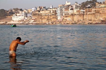 VARANASI, INDIA - FEBRUARY 20, 2012: An Unidentified pilgrim offers prayer to holy Ganges river on Maha Shivaratri festival on February 20, 2012 at Varanasi, Uttar Pradesh, India. Stock Photo - 13686142