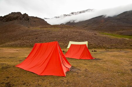 monsoon clouds: Swiss tents at a campsite near Chandertal lake in Himalaya mountain valley