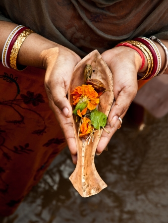 Hands of a Hindu pilgrim offering prayer to river goddess Ganges