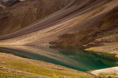 Clear reflection of the colorful mountains in the turquoise water of Chandratal lake