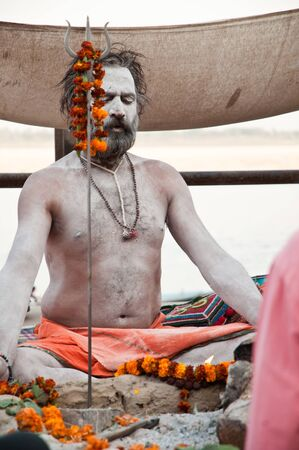 VARANASI, INDIA - MARCH 10: A hindu saint meditates during rituals of Lord Shiva prayer on the auspicious Maha Shivaratri festival on March 10, 2013 at Varanasi, Uttar Pradesh, India. Stock Photo - 18646849