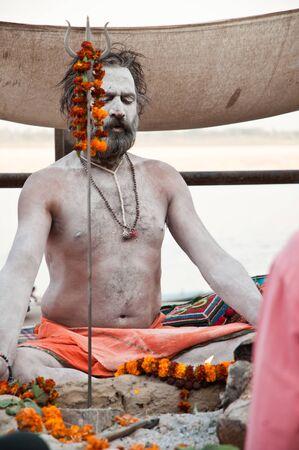 meditates: VARANASI, INDIA - MARCH 10: A hindu saint meditates during rituals of Lord Shiva prayer on the auspicious Maha Shivaratri festival on March 10, 2013 at Varanasi, Uttar Pradesh, India.