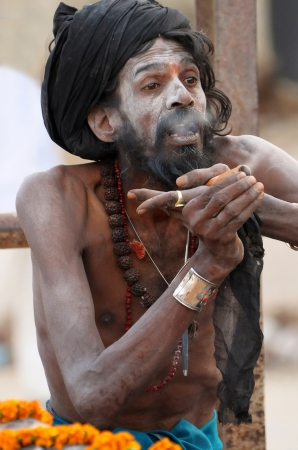 VARANASI, INDIA - FEBRUARY 20: A shaiva sadhu smokes pot during prayer on the auspicious Maha Shivaratri festival on February 20, 2012 at Varanasi, Uttar Pradesh, India. Stock Photo - 18646847