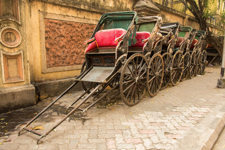 ancient india: Traditional hand pulled Indian rickshaws parked together in front of a old building in Kolkata Stock Photo