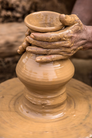 clay craft: Hands of a clay artisan working to make a flower vase out of soft clay on a rotating cart wheel Stock Photo