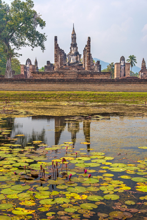 sukhothai: Statue of seated Buddha in meditation reflected across a lotus pond in Wat Mahathat temple in Sukhothai, Thailand. Stock Photo