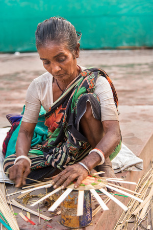 west bengal: KOLKATA, INDIA - DECEMBER 11: An Indian craftswoman weaves a cane basket for sale during the annual State Handicrafts Expo 2014 on December 11, 2014 in Kolkata, West Bengal, India. Editorial