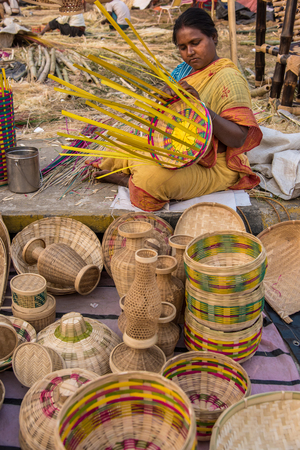 craftswoman: KOLKATA, INDIA - DECEMBER 11: An Indian craftswoman weaves a cane basket for sale during the annual State Handicrafts Expo 2014 on December 11, 2014 in Kolkata, West Bengal, India. Editorial