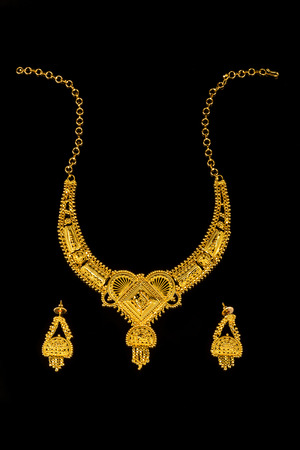 comprising: Beautiful and expensive glittering gold jewelery set comprising of necklace and ear rings