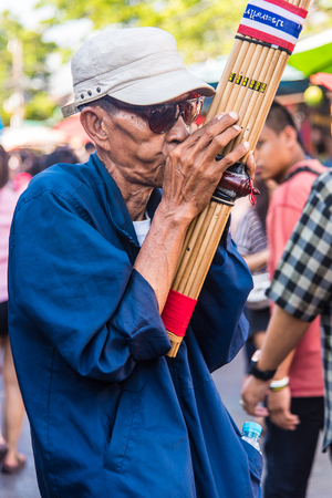 melodious: BANGKOK, THAILAND - FEBRUARY 22: An unidentified street musician performs at Chatuchak market on February 22, 2015 in Bangkok, Thailand.
