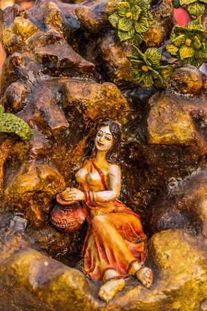 cultural and ethnic clothing: Beautiful clay doll of a miniature village girl bathing in a mountain stream. Stock Photo