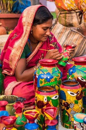 craftswoman: KOLKATA; INDIA - NOVEMBER 24: An Indian craftswoman paints on colorful handicraft items for sale during the annual State Handicrafts Expo 2015 on November 24; 2015 in Kolkata; West Bengal; India.