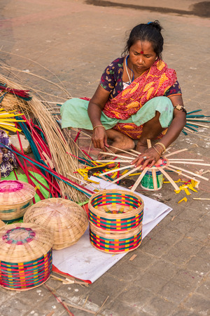 craftswoman: KOLKATA, INDIA - NOVEMBER 24: An Indian craftswoman weaves cane baskets for sale during the annual State Handicrafts Expo 2015 on November 24, 2015 in Kolkata, West Bengal, India.