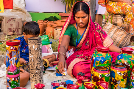 craftswoman: KOLKATA, INDIA - NOVEMBER 24: A craftswoman paints on colorful handicraft items with her son during the annual State Handicrafts Expo 2015 on November 24, 2015 in Kolkata, West Bengal, India. Editorial