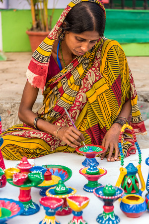 craftswoman: KOLKATA, INDIA - NOVEMBER 24: An Indian craftswoman paints on colorful handicraft items for sale during the annual State Handicrafts Expo 2015 on November 24, 2015 in Kolkata, West Bengal, India.