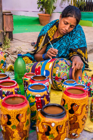 west bengal: KOLKATA, INDIA - NOVEMBER 24: An Indian craftswoman paints on colorful handicraft items for sale during the annual State Handicrafts Expo 2015 on November 24, 2015 in Kolkata, West Bengal, India.