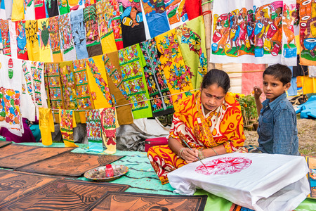craftswoman: KOLKATA, INDIA - NOVEMBER 28: An Indian craftswoman with his child paints on colorful handicraft items for sale during the annual State Handicrafts Expo 2015 on November 28; 2015 in Kolkata, West Bengal, India. Editorial