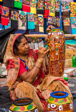 craftswoman: KOLKATA, INDIA - NOVEMBER 28: An Indian elderly craftswoman paints on colorful handicraft items for sale during the annual State Handicrafts Expo 2015 on November 28, 2015 in Kolkata, West Bengal, India.