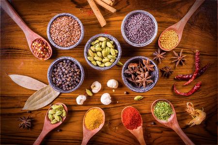 Assortiment van kruiden en specerijen in houten lepels en stenen Spice kommen over gepolijste geweven houten plank.