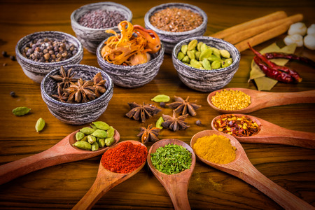 Indian herbs and spices beautifully arranged in wooden spoons and stone bowls arranged over wooden textured table Stok Fotoğraf