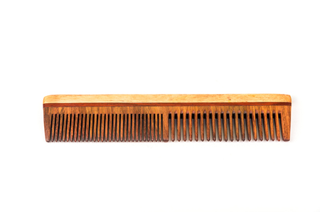 Classic wooden comb with dual sized bristles over white background