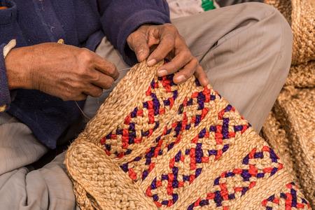 craftswoman: Hands of a craftsman weaving handicraft items made of jute Stock Photo