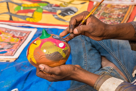 earthen pot: Close up of the hands of a artist painting colorful earthen pot piggy bank. Stock Photo