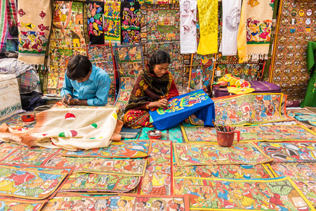 indian fair: SHANTINIKETAN, INDIA - DECEMBER 25: An Indian artist couple paints on colorful handicraft items for sale during the annual Poush Mela fair 2015 on December 25, 2015 in Shantiniketan, West Bengal, India.