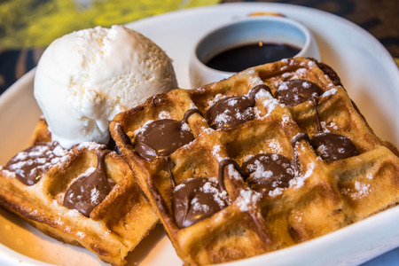 Delicous crispy nutella waffle with ice-cream and chocolate syrup and caramel topping