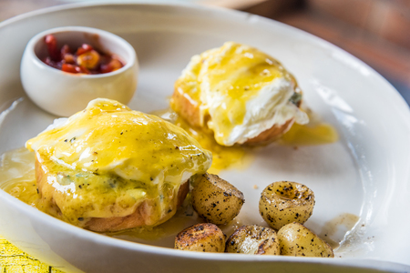 French Benedict breakfast: Two poached eggs on English muffin, doused generously with homemade hollandaise and served with soupy corn and parsley potatoes. Stock Photo