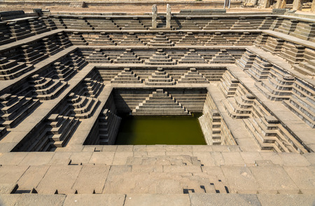 The famous ancient Stepped Tank in Hampi, excavated from ruins of 14th century Vijayanagara kingdom. Stock Photo